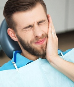 A patient holding his mouth in pain.