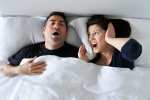 a man snoring and his wife covering her ears