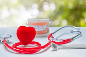 Red heart shape sitting next to model teeth and stethoscope