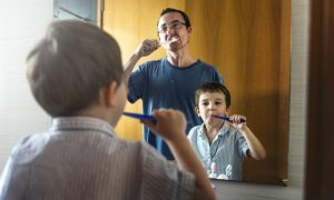 Father and son brushing to protect their immune systems.