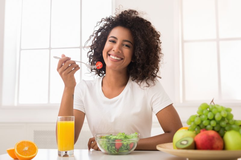 young woman smiling and eating healthy foods