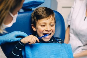 young boy brushing his teeth while visiting his children's dentist in Freedom
